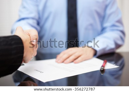 Businessman and businesswoman are handshaking over signed contract, partnership concept - stock photo