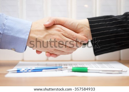 businessman and businesswoman are handshaking over signed contract with binders in background - stock photo