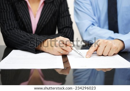 businessman and businesswoman are pointing to article of the treaty - stock photo