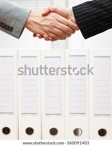 businessman and businesswoman are shaking hands over company documents - stock photo
