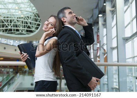 Businessman and Businesswoman back to back on mobile phones - stock photo