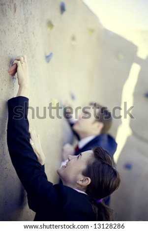 businessman and businesswoman climbing to the top of the wall - stock photo