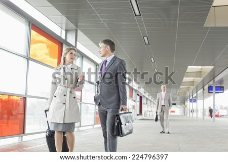 Businessman and businesswoman conversing while walking in railroad station - stock photo