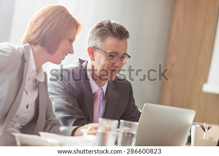 Businessman and businesswoman discussing while having lunch in office - stock photo