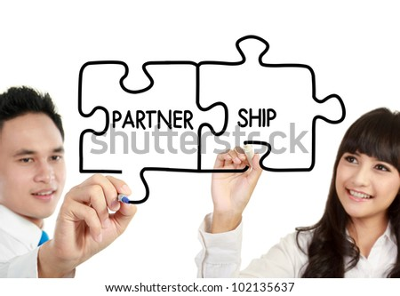"businessman and businesswoman drawing ""partnership"" written in puzzle - stock photo"