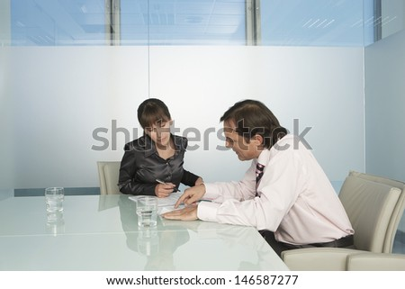 Businessman and businesswoman going through documents in conference room - stock photo
