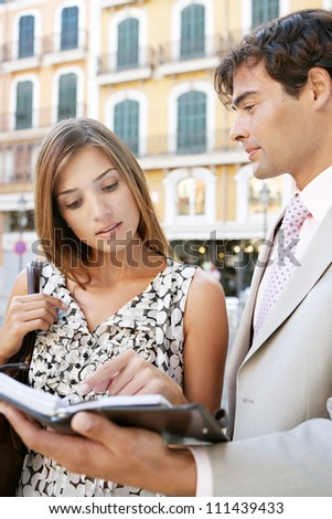 Businessman and businesswoman having a meeting outdoors, in a classic city, and looking at paperwork. - stock photo