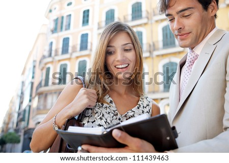 Businessman and businesswoman having a meeting outdoors, in a classic city, and looking at paperwork and smiling. - stock photo