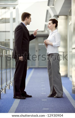 Businessman and businesswoman having argument in modern office building corridor - stock photo