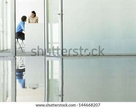 Businessman and businesswoman in meeting viewed through open office door - stock photo