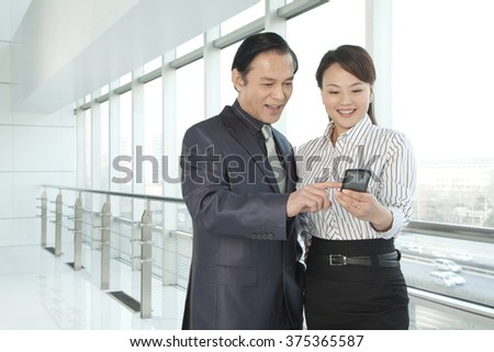 Businessman and Businesswoman looking a phone - stock photo