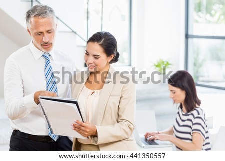 Businessman and businesswoman looking at diary while a colleague working on laptop in the background - stock photo