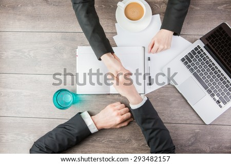 Businessman and businesswoman meeting Handshake. Hand holding. Top view for top managers.  White paper, where you can place your text or information - stock photo