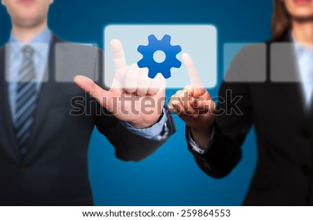 Businessman and Businesswoman pressing Gear Button and Ticking Check Box - stock photo