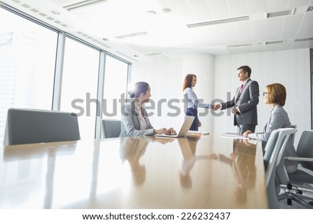Businessman and businesswoman shaking hands in conference room - stock photo