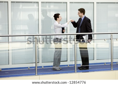 Businessman and businesswoman shaking hands on modern office corridor. - stock photo