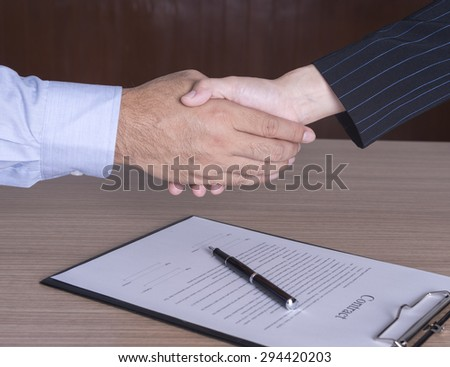 businessman and businesswoman shaking hands to congratulate to be working well. - stock photo