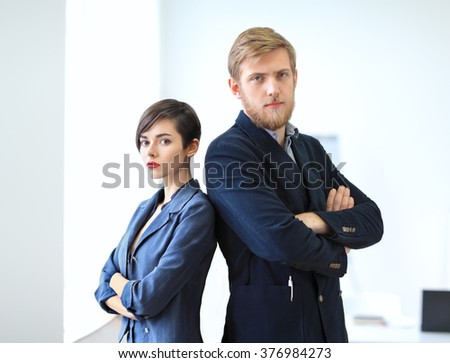 Businessman and businesswoman standing back to back with crossed arms in the office. Team work concept. - stock photo