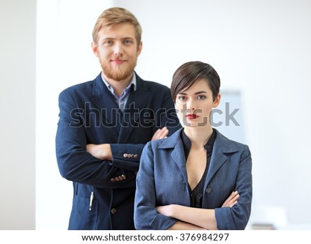 Businessman and businesswoman standing with crossed arms in the office. Team work concept. - stock photo