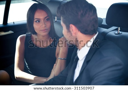 Businessman and businesswoman talking in back seat of car - stock photo