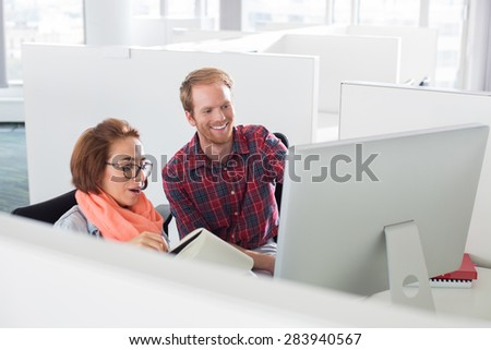 Businessman and businesswoman using computer in creative office - stock photo