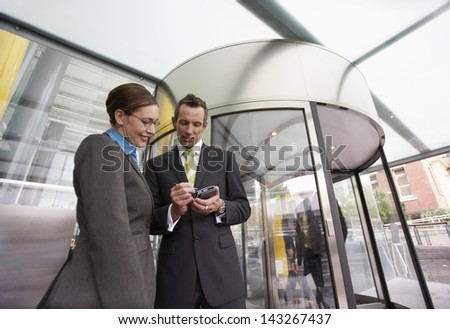 Businessman and businesswoman using PDA in front of revolving door - stock photo