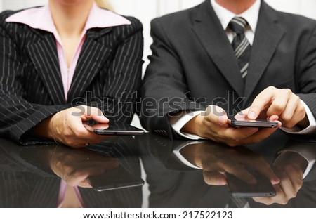 businessman and businesswoman using smart phone on meeting - stock photo