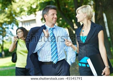 Businessman and businesswoman walking and talking in downtown park. - stock photo