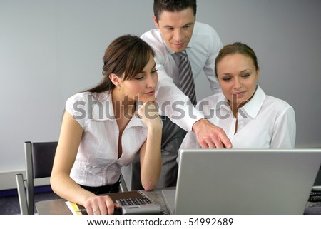 Businessman and businesswomen in front of a laptop computer - stock photo