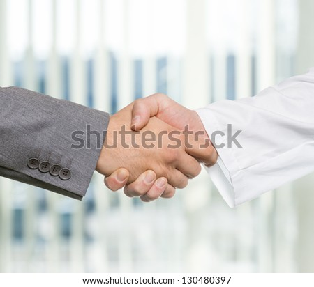 Businessman and doctor shaking hand's in office - stock photo