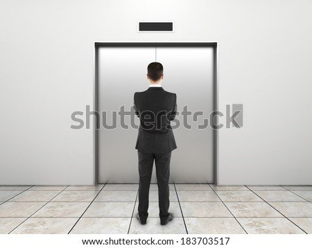 businessman and elevator with closed doors - stock photo