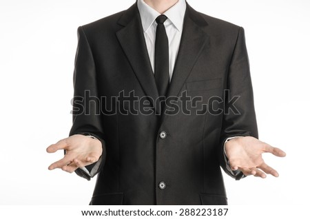 Businessman and gesture topic: a man in a black suit and tie holding hands in front isolated on white background in studio - stock photo