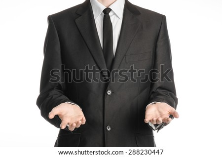 Businessman and gesture topic: a man in a black suit and tie holding two hands in front isolated on white background in studio - stock photo