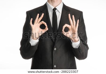 Businessman and gesture topic: a man in a black suit with a tie showing two hands sign of okay isolated on white background in studio - stock photo