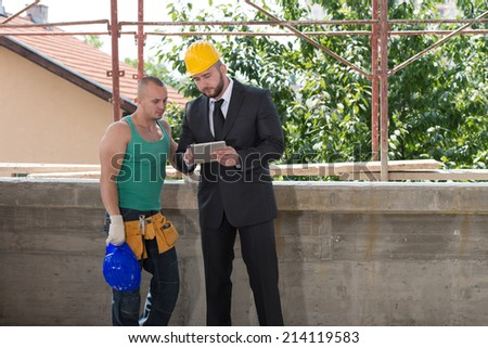 Businessman And Industrial Worker Looking At Tablet PC - stock photo