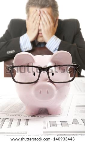Businessman and pink piggy bank - stock photo