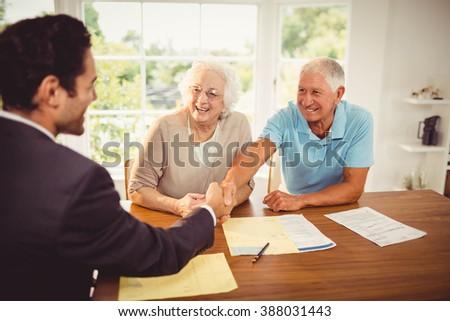 Businessman and senior man handshaking at home - stock photo