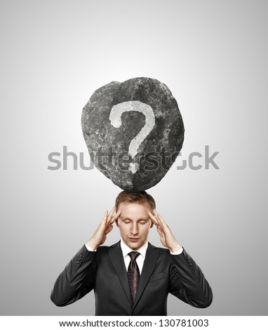 businessman and stone with question on his head - stock photo