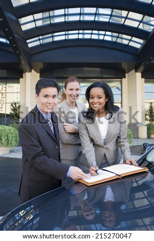 Businessman and two businesswomen signing contract outside hotel, leaning on car, smiling, portrait - stock photo