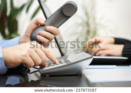 businessman and woman are contacting new clients  over telephone and internet - stock photo