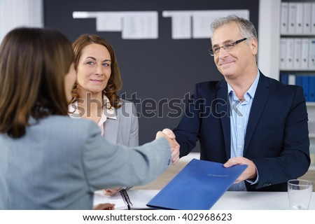 Businessman and woman conducting an interview smiling as they congratulate and shake hands with the prospective applicant while holding her CV - stock photo