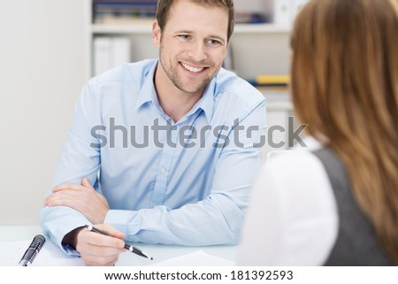 Businessman and woman in a meeting as he sits at a desk smiling with paperwork in front of him and a pen in his hand, view over her shoulder - stock photo