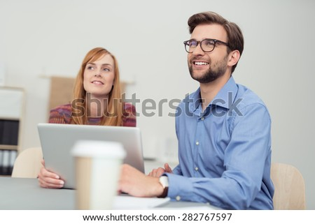 Businessman and woman in a meeting sitting at an office table both looking up with a smile as they watch and listen to a presentation - stock photo