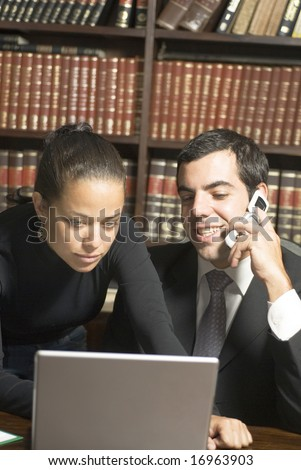 Businessman and woman looking at laptop and talking on phone. Vertically framed photo. - stock photo