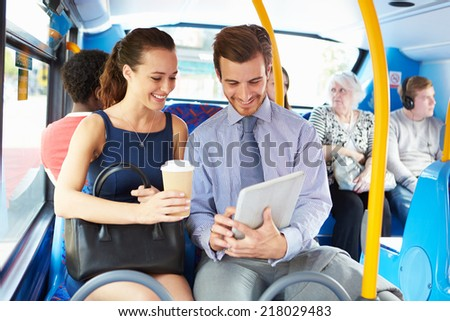 Businessman And Woman Using Digital Tablet On Bus - stock photo