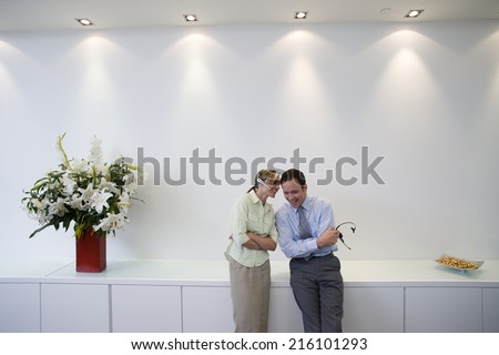Businessman and woman with headsets in conversation, smiling - stock photo