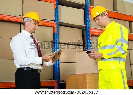 Businessman And Worker Using Digital Tablet And Mobile Phone In Warehouse - stock photo