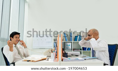 Businessman annoyed by the phone calls of his colleague - stock photo