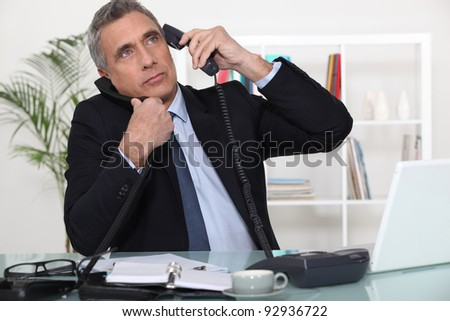 Businessman answering ringing telephones - stock photo