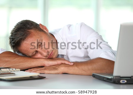 Businessman asleep on his desk - stock photo